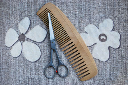 Professional scissors and wooden comb on natural background photo
