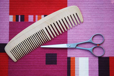 Professional scissors and wooden comb on colorful background photo