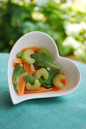 Various vegetables in heart shape bowl on green natural background photo