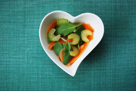 Various vegetables salad in heart shape bowl on green background