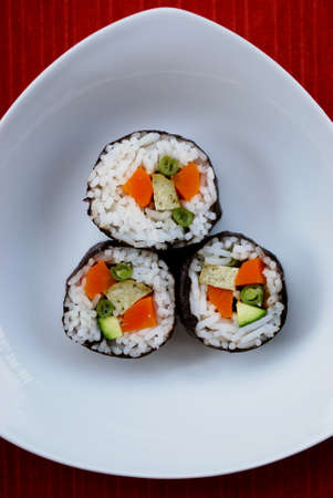 Vegetarian maki sushi rolls with rice, carrots, zucchini, green beans, tofu and nori seaweed in white dish on red background Stock Photo