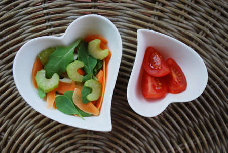 Various vegetables salad in two heart shape bowls on natural background Stock Photo