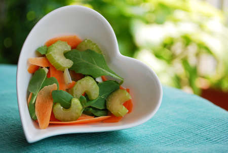 Various vegetables salad in heart shape bowl on green natural background Stock Photo - 22750460