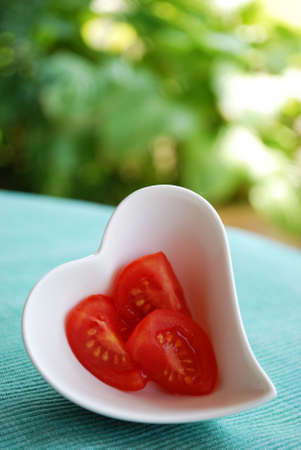 Red tomatoes salad in heart shape bowl on green natural background