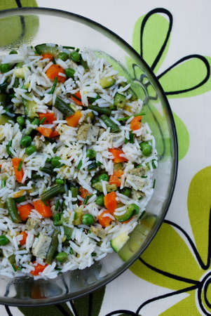 Vegetarian salad of white basmati rice with carrots, zucchini, green beans, peas, tofu and chives in a glass bowl on colorful background