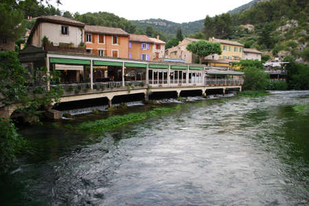 Fontaine de Vaucluse village on Sorgue river clean green water, Provence, France