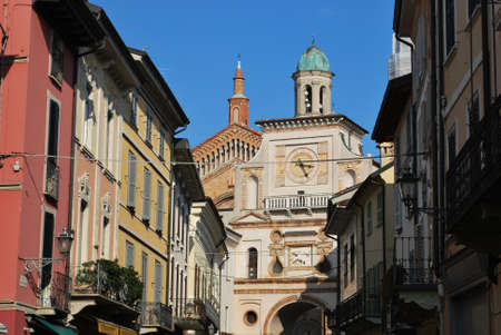 Ancient houses and clock arch entrance to cathedral square, Crema town, Lombardy, Italy