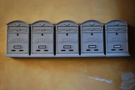 A row of gray color mailboxes in vintage style on old yellow wall Stock Photo
