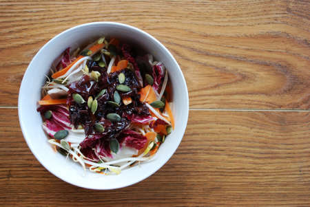Red salad with carrots, sprouts, pumpkin seeds and seaweed in white bowl on wooden  Stock Photo