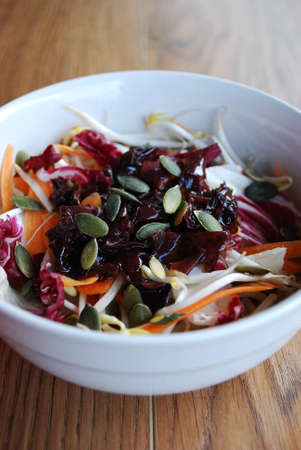 Red salad with carrots, sprouts, pumpkin seeds and seaweed in white bowl on wooden  photo