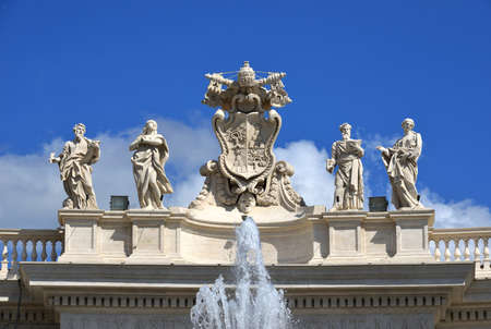 Detail from baroque Saint Peters colonnade with beautiful statues of saints and Pope Alexander VII coat of arms