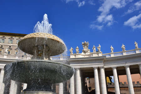 bernini: Beautiful baroque fountain and colonnade with statues of saints, designed by the famous artitst Bernini in the 17th century in Saint Peters Square Rome