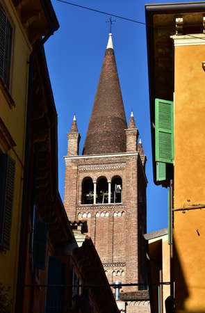 spire: Conical spire of SantEufemia gothic church seen from the narrow street of Verona historical center