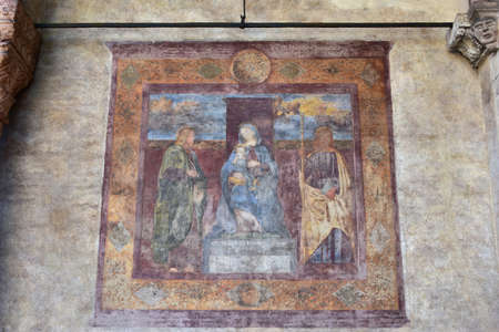 jesus paintings: Beautiful fresco with Virgin Mary and Jesus among two saints, painted by the artist Francesco Moroni in the 16th century, just outside San Fermo Maggiore church side portal Stock Photo