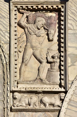 capturing: Detail of Saint Mark Bailica facade with relief of the Fouth Labor of Hercules, capturing the Erymanthian Boar and carried it back to the frightend Eurystheus (13th century)