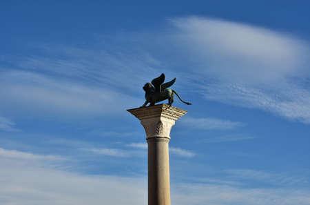 leon con alas: estatua de bronce de San Marcos Le�n con alas entre las nubes, en la parte superior de una columna antigua en Venecia Foto de archivo