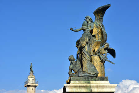italian people: Bronze sculptoral group cast by artist Monteverde in 1911 with statues symbolizes: genius thought, discord, Minerva goddess and Italian people rising from tyranny. Trajan column in the background with St Peter statue. Stock Photo