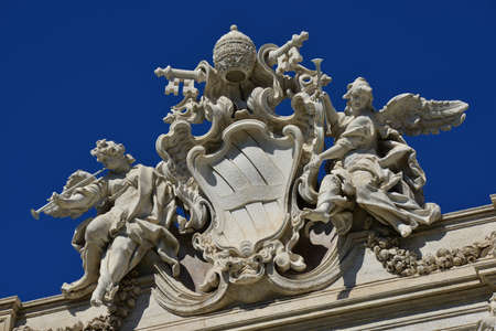 angels fountain: Emblem of Pope Clement XII among angels with trumpets, at the top of Trevi Fountain in Rome Stock Photo
