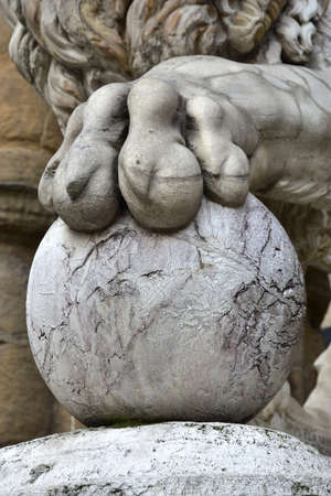 lion claw: Doctors Lion holds the globe in Piazza della Signoria. Detail of the claw from marble lion statues at the entrance (left side) of the Loggia dei Lanzi in Florence, made by artist Flaminio Vacca in 1598 Stock Photo
