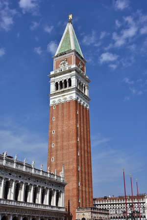 saint mark square: Saint Marks bell tower, the tallest belfry in Venice and one of the city landmark, with old National Library Stock Photo