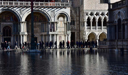 saint mark square: Venice, Italy, November 27, 2015: High tide flooding Saint Mark Square in Venice, with people walking on a footbridge Editorial