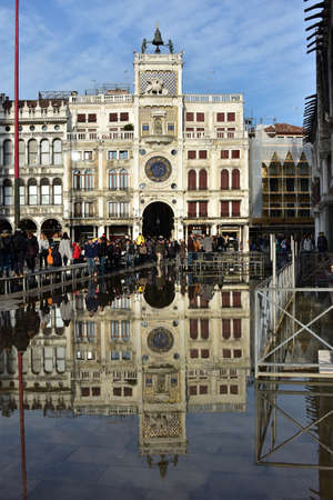 saint mark square: Venice, Italy, November 28, 2015: High tide flooding Saint Mark Square in Venice and tourists walking on footbridge before the famous Clock Tower Editorial