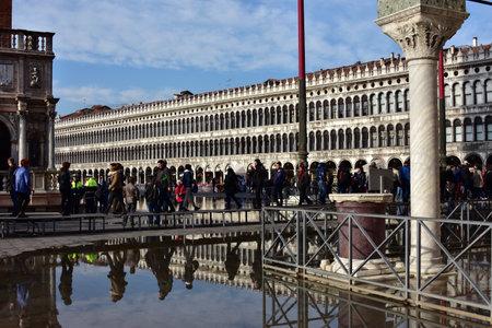 saint mark square: Venice, Italy, November 28, 2015: High tide flooding Saint Mark Square in Venice and tourists walking on footbridge
