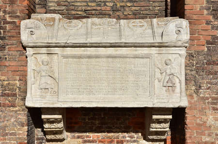 doge: Marble sarcophagus with angels, cross and doge hat symbol, on St John and Paul basilica gothic facade in Venice Stock Photo