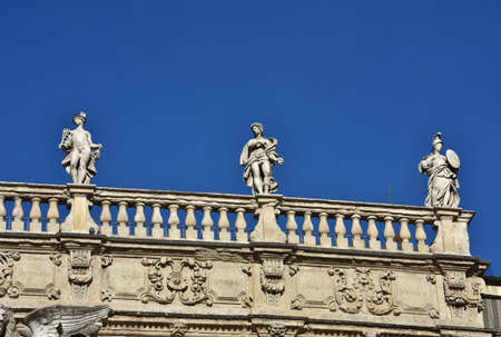 minerva: Monumental baroque balustrade of Palazzo Maffei (17th century) with greek gods statues of Mercury, Apollo and Minerva, in Piazza delle Erbe square, in the center of Verona