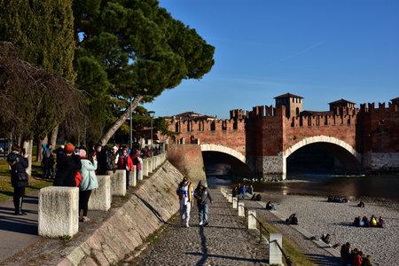 embrasure: Verona, Italy, February 5, 2016: Tourists visit medieval Scaliger Bridge and Adige River banks in Verona