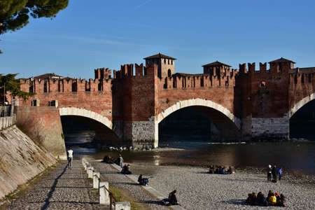 embrasure: Verona, Italy, February 5, 2016: People on Adige river bank and medieval Scaliger Bridge Editorial