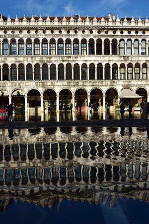 procuratie: Venice, Italy, November 28, 2015: Reflection of Old Procuratie in Saint Mark Square during High Water (Venice high tide) Editorial