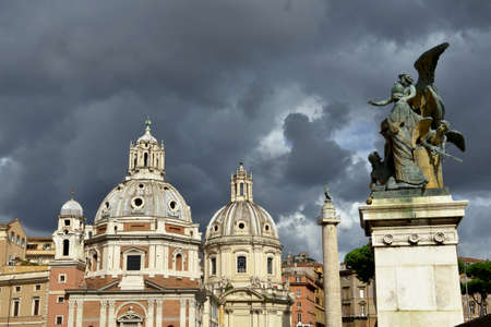 View of the Trajans Forum twin churches dedicated to Virgin Mary from Altar of Nation monument and in front of ancient victory column, with cloudy sky Stock Photo