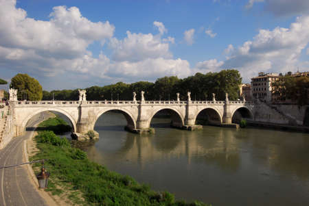 architecture monumental: The famous Holy Angel Bridge across River Tiber, with beautiful baroque statues and clouds, in the historic center of Rome