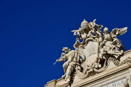 Emblem of Pope Clement XII between angels with trumpets, at the top of the beautiful Trevi Fountain in Rome (with copy space) Stock Photo