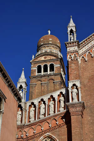 Bell tower of Santa Maria dellOrto church in Venice, among gothic statues (15th century)