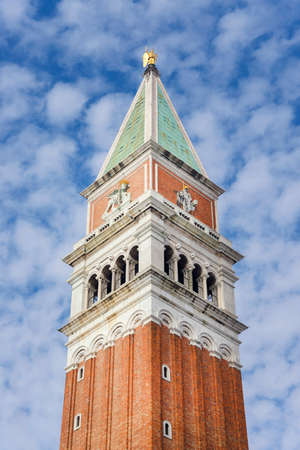 crown spire: Saint Mark bell tower in the center of Venice with golden angel statue at the top and beautiful clouds
