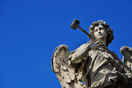 Angel marble statue with sponge, a 17th century baroque masterpiece on Holy Angel Bridge in Rome (with blue sky and copy space) Banque d'images