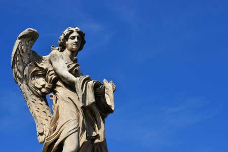Statue en marbre d'ange avec du vêtement et des dés, un chef-d'oeuvre baroque du XVIIe siècle sur le pont de l'Ange Saint-Pierre à Rome (avec ciel bleu et espace copie)