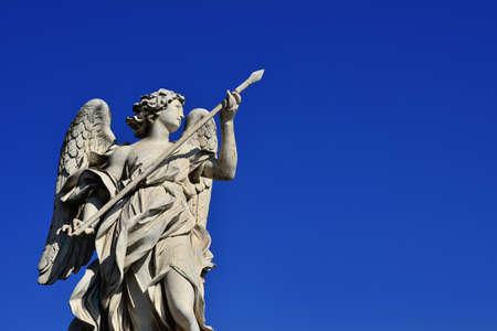 Statue d'ange tenant la Sainte Lance de Longinus sur le pont de Sant'Angelo à Rome (avec ciel bleu et copie d'espace)