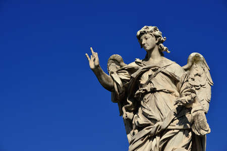 Angel statue holding the Nails of Jesus Cross on SantAngelo Bridge in Rome (with blue sky and copy space)