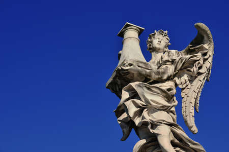 Angel statue holding the Column of Jesus Passion looks at the Heaven on SantAngelo Bridge in Rome (with blue sky and copy space) Stock Photo