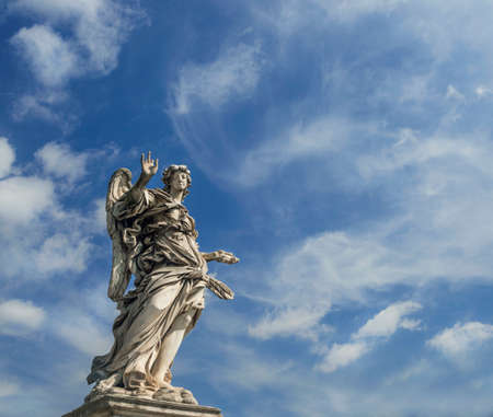 Angel statue holding the Nails of Holy Cross with heavenly sky on SantAngelo Bridge in the center of Rome Stock Photo