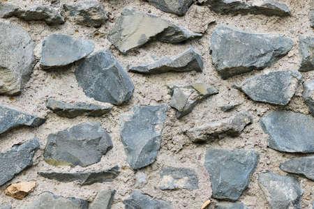 Roche de lave sombre et fond de mur ancien en béton Banque d'images