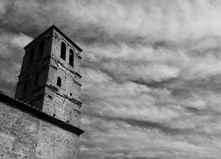 Le beffroi médiéval de l'église de San Giuliano avec des nuages, au centre de l'ancien ruiné de Faleria, une petite ville près de Rome (noir et blanc) Banque d'images