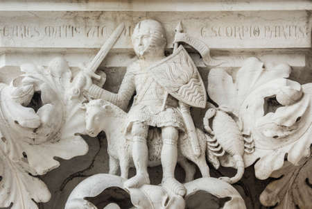 Planet Mars as knight with Aries and Scorpio zodiac signs, ancient medieval relief on Venice Doge Palace column