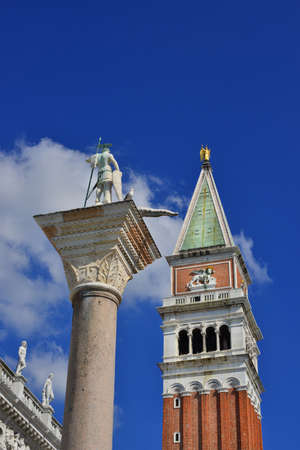 lion wings: Saint Theodore ancient column and Saint Mark bell tower in the center of Venice (with blue sky and copy space)