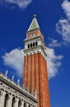 Le clocher de Saint-Marc avec l'ange doré au sommet avec le ciel bleu et les nuages, au centre de Venise