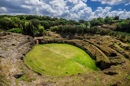 Ancient roman tuff stone amphitheater in the town of Sutri with clouds, near Rome