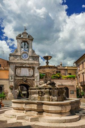 Place principale de Sutri dans le centre-ville historique avec fontaine, ancienne tour de l'horloge et nuages Éditoriale